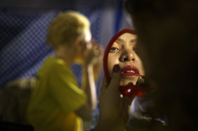 A contestant checks her makeup in a mirror as she prepares to perform in the Mr. & Miss Albinism East Africa contest, organized by the Albinism Society of Kenya, in Nairobi, Kenya Friday, November 30, 2018. The event aims to promote social inclusion and raise the self-esteem of albinos, who frequently face discrimination and stigma. (Photo by Ben Curtis/AP Photo)