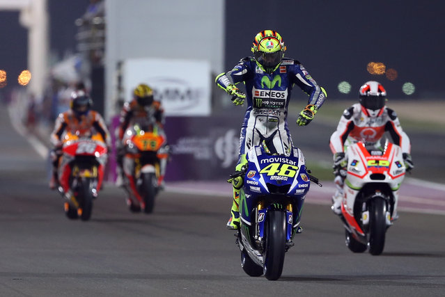 MotoGP rider Valentino Rossi of Italy, center, performs a wheelie during a free practice at the Losail International Circuit in Doha, Qatar, Thursday, March 26, 2015. (Photo by Osama Faisal/AP Photo)