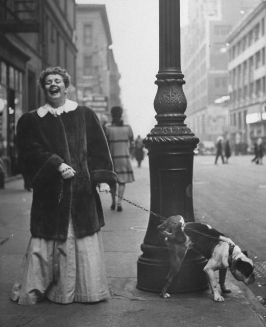 Leen photographed European royalty, Paris fashion and American teens for Life, but her first picture for the magazine was taken at the Bronx Zoo and she returned to photographing animals throughout her career. Here: actress Joan Roberts clad in costume for the musical Oklahoma, roaring w. laughter as her English bulldog Goggles lifts his leg on a streetlight. (Photo by Nina Leen/Pix Inc./The LIFE Picture Collection/Getty Images)