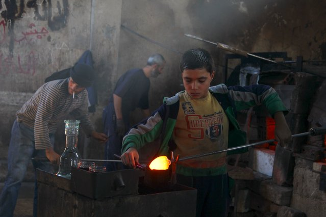 An artisan boy casts heated glass at a factory that recycles glass in Idlib countryside, Syria November 9, 2015. (Photo by Ammar Abdullah/Reuters)