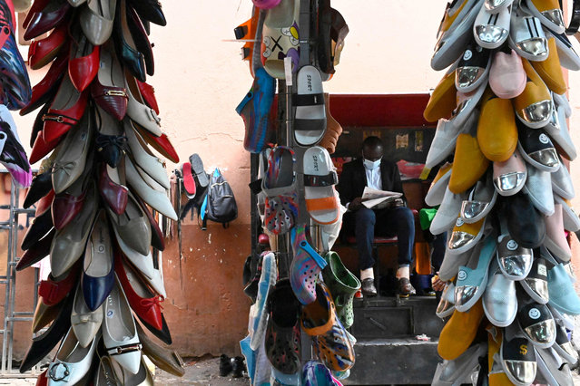 A man reads a newspaper next to a shoe shop in down town Nairobi on July 14, 2021. (Photo by Simon Maina/AFP Photo)