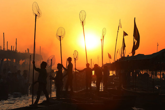 Indian fishermen are silhuetted by the rising sun as they prepare for an early  morning catch at the banks of Narmada river in Nemawar district Dewas, 200 kilometers from Bhopal, Madhya Pradesh, India 20 March 2015. (Photo by Sajneev Gupta/EPA)