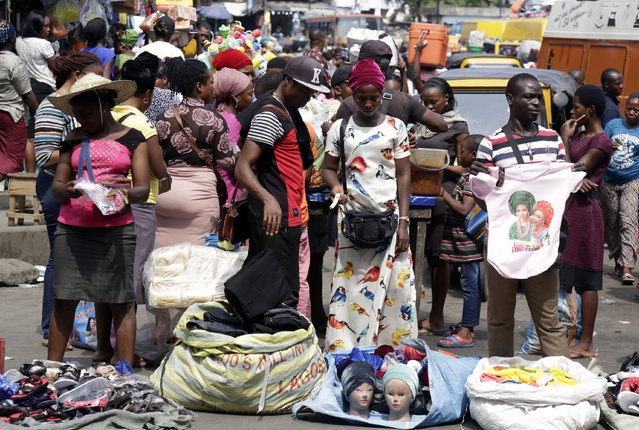 In this Tuesday, September 5, 2017 file photo, pedestrians shop at a busy Balogun Market in Lagos, Nigeria. The report released Monday, Oct. 29, 2018 says Africa's overall GDP has risen nearly 40 percent over the past decade but the continent's average score for sustainable economic opportunity has increased just a fraction of 1 percent. (Photo by Sunday Alamba/AP Photo)