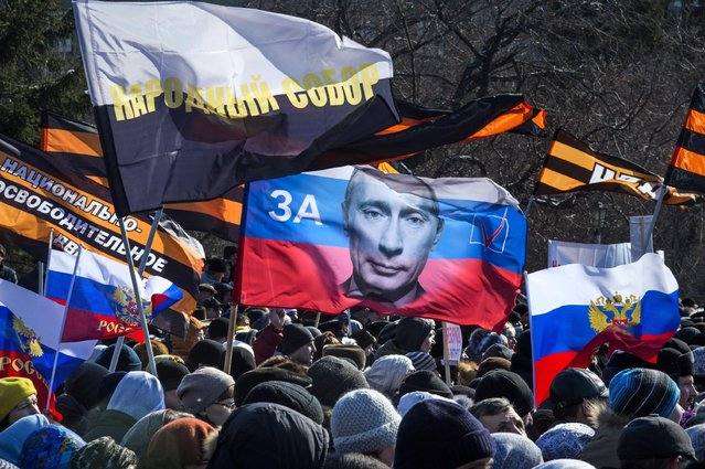 """Several thousand people carry patriotic flags as they demonstrate against the proposed production of Wagner's Tannhauser, in downtown Novosibirsk, about 2800 kilometers (1,750 miles) east of Moscow, Sunday, March 29 2015. Controversy over the staging of Wagner's opera """"Tannhauser"""" in the Siberian city has come to a head, with Russia's cultural minister firing the director of the state theater in Novosibirsk. (Photo by Ilnar Salakhiev/AP Photo)"""