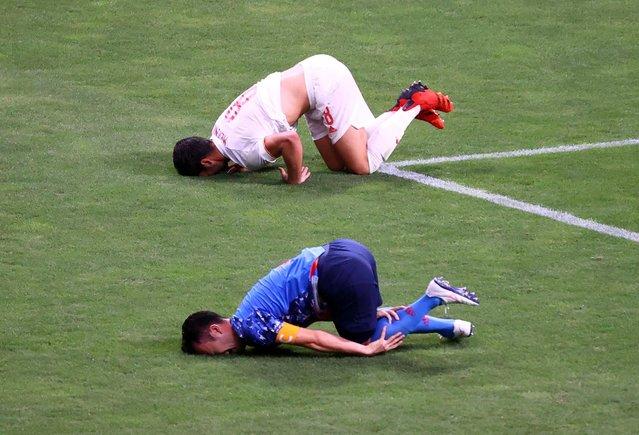 Mikel Merino of Spain and Maya Yoshida of Japan react on the pitch following a collision during the Tokyo 2020 Olympic Games men's semi-final football match between Japan and Spain at Saitama Stadium in Saitama on August 3, 2021. (Photo by Kim Hong-Ji/Reuters)
