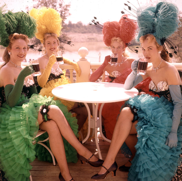 A quartet of showgirls in costume sit at an outdoor table and drink from mugs at Disneyland amusement park, Anaheim, California, 1955. (Photo by Loomis Dean/The LIFE Picture Collection/Getty Images)
