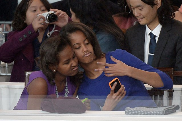 Sasha (L) and Malia Obama, daughters of US President Barack Obama, take a photo of themselves during the Presidential Inaugural Parade on January 21, 2013 in Washington, DC. (Photo by Joe Klamar/AFP Photo)