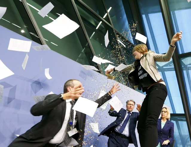 Security officers catch a protester who jumped on the table in front of the European Central Bank President Mario Draghi during a news conference in Frankfurt, April 15, 2015. (Photo by Ralph Orlowski/Reuters)