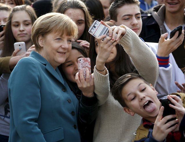 Pupils take selfies with German Chancellor Angela Merkel, as she arrives for a visit at Robert-Jungk Europe high school as part of the Europe-Project Day, in Berlin in this March 31, 2014 file photo. (Photo by Fabrizio Bensch/Reuters)