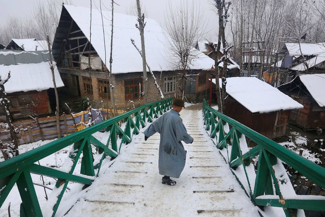 A young Kashmiri boy slides down a snow covered wooden bridge after fresh snowfall, in the outskirts of Srinagar, India, Thursday, January 9, 2014. Traffic on the 300 kilometers (186 miles) long Jammu-Srinagar national highway has been suspended due to heavy snowfall, according to news reports. (Photo by Dar Yasin/AP Photo)