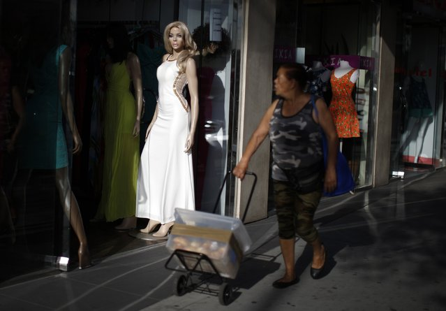 A woman walks past a store mannequin in Los Angeles, California March 17, 2015. (Photo by Lucy Nicholson/Reuters)