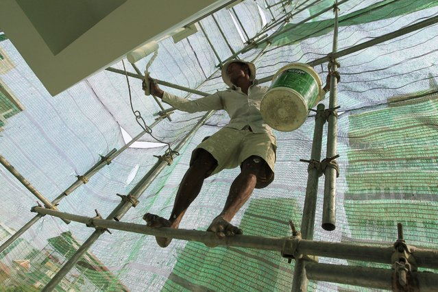 A Cambodian worker balances on a scaffolding as he works at a construction site in Phnom Penh, Cambodia, 02 March 2016. The Cambodian Ministry of land management and building has allowed 2,305 projects to construction companies for the whole country in 2015, and an investment of approximately 3,3 billion US dollars for the constructions, meaning a 33.1 per cent increas compare to 2014, local media said. (Photo by Kith Serey/EPA)