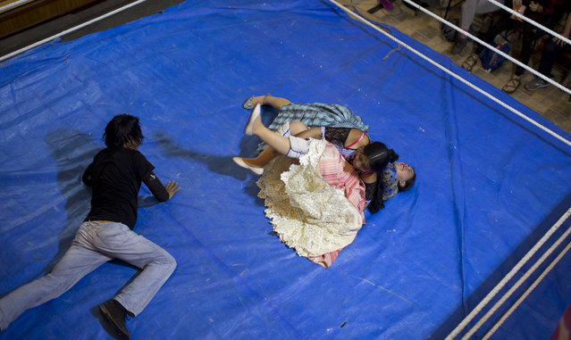 Cholita wrestler Natalia Pepita, 19, is held down by fellow fighter in training, Wara, 22, in the ring in El Alto, Bolivia, Thursday, February 7, 2019. A new generation of about 50 athletes are training to a wrestle in traditional billowing skirts, bowler hats and the leather shoes of Aymara women. (Photo by Juan Karita/AP Photo)