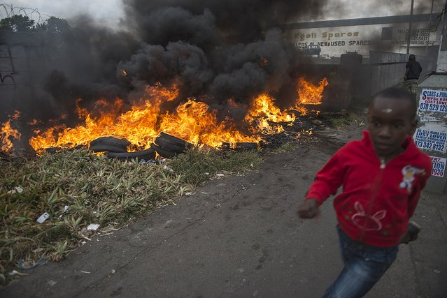 A child runs pass burning tires during the xenophic violence, on 17 April 2015 in Jeppestown area of central Johannesburg. Twelve people were arrested overnight as anti-foreigner attacks in South Africa spread to parts of downtown Johannesburg, police said. According to local reports, the protesters from a local hostel demanded foreign nationals leave South Africa, setting cars alight and clashing with police. (Photo by Mujahid Safodien/AFP Photo)