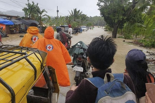 In this handout photo provided by the Philippine Red Cross, volunteers and residents cross a flooded road due to typhoon Conson at Usab village, Masbate province, central Philippines on Tuesday September 7, 2021. Typhoon Conson slammed into the eastern Philippines, causing power outages, suspension of work in government offices, and flooding in some areas on Tuesday. Weather bureau later said Conson weakened into a severe tropical storm. (Photo by Philippine Red Cross via AP Photo)