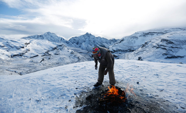 """Aymara priest Valentin Apaza stands over a burning offering for the """"Pachamama"""", or Mother Earth, during a ceremony on La Cumbre, a mountain considered sacred ground on the outskirts of La Paz, Bolivia, Wednesday, April 22, 2015. The world marks Earth Day on April 22 to increase awareness and to promote practices for the sustainability and protection of the Earth's natural environment. (Photo by Juan Karita/AP Photo)"""
