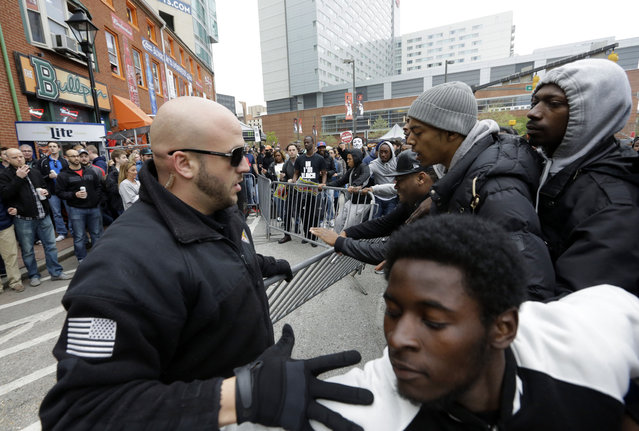 Protestors pull a barrier down outside of a bar across the street from Oriole Park at Camden Yards after a rally for Freddie Gray, Saturday, April 25, 2015, in Baltimore. (Photo by Patrick Semansky/AP Photo)