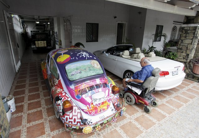 """Rene Penia sits in an electrical wheel chair and in between a VW Beetle 1995, locally called """"Vocho"""", and another one of his cars, outside his home in Monterrey April 22, 2015. (Photo by Daniel Becerril/Reuters)"""