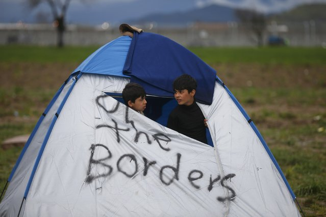 Migrant children stand in a tent at a makeshift camp on the Greek-Macedonian border near the village of Idomeni, Greece March 10, 2016. (Photo by Stoyan Nenov/Reuters)