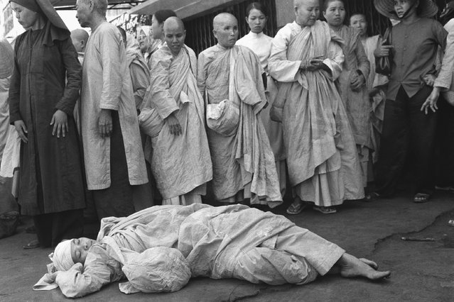 South Vietnamese Buddhist nun injured in melee between police and about 20 nuns staging demonstration rests on floor at pagoda surrounded by other activist religious in Saigon, Sunday, Jan. 26, 1975. Antigovernment protest and fighting followed political convention. Four nuns were injured, none of them seriously. (Photo by Nguyen Tu A/AP Photo)