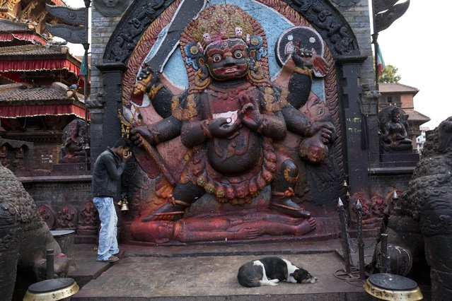 A man offers prayers to Hindu God Bhairav at Basantapur Durbar Square, a lot of which was damaged in Saturday's earthquake, in Kathmandu, Nepal, Sunday, April 26, 2015. The earthquake centered outside Kathmandu, the capital, was the worst to hit the South Asian nation in over 80 years. It destroyed swaths of the oldest neighborhoods of Kathmandu, and was strong enough to be felt all across parts of India, Bangladesh, China's region of Tibet and Pakistan. (Photo by Bernat Armangue/AP Photo)