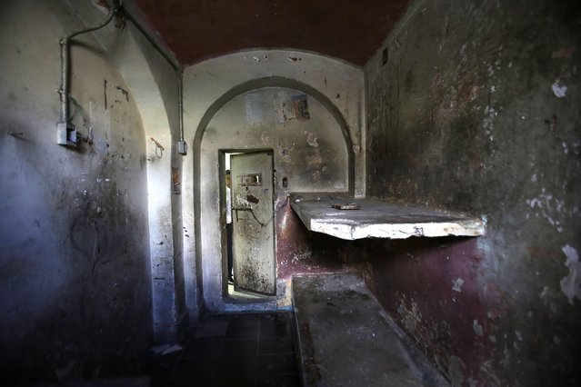 "In this April 7, 2015 photo, a tourist peers through the door of a jail cell inside the now empty Garcia Moreno prison during a guided tour for the public in Quito, Ecuador. According to tour guides, this cell was nicknamed ""Los Polillas"", or ""The Moths"". Here, in a room designed to hold two prisoners, about 15 inmates with drug addictions were locked in overnight by the prison gangs that controlled daily life. The locked-in prisoners were also known to prostitute themselves to get access to drugs. (Photo by Dolores Ochoa/AP Photo)"