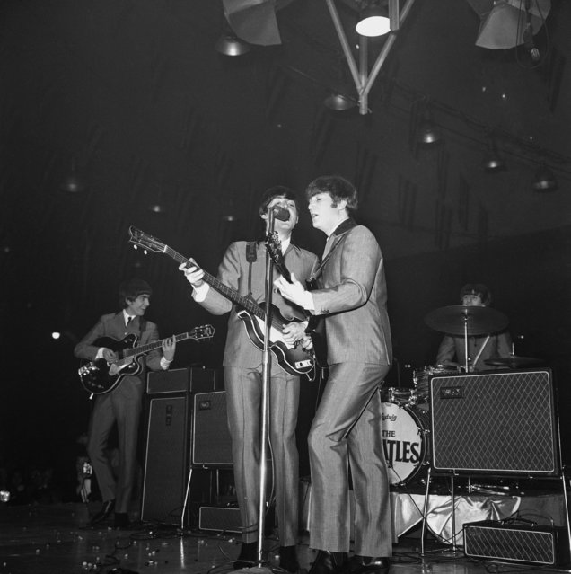 Surrounded by amplifiers and treading jumping beans underfoot, the Beatles swing into their routine during a show at the Coliseum in Washington, February 11, 1964. From left: lead guitarist George Harrison, bassist Paul McCartney, rhythm guitarist John Lennon, and drummer Ringo Starr. The beans were thrown by excited fans. (Photo by AP Photo)