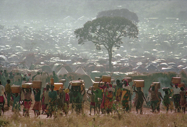 In this May 17, 1994, file photo, refugees who fled the ethnic bloodbath in neighboring Rwanda carry water containers back to their huts at the Benaco refugee camp in Tanzania, near the border with Rwanda. With a population surpassing 300,000, aid agencies are having difficulty feeding, treating and sheltering them. (Photo by Karsten Thielker/AP Photo/File)
