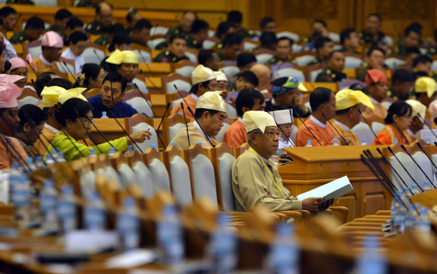 Htin Kyaw, foreground, the newly elected president of Myanmar, attends a session in Myanmar parliament in Naypyitaw, Myanmar, Friday, March 18, 2016. Myanmar's parliament elected Htin Kyaw as Myanmar's new president on March 15, 2016, a watershed moment that ushers the longtime opposition party of Aung San Suu Kyi into government. (Photo by Aung Shine Oo/AP Photo)