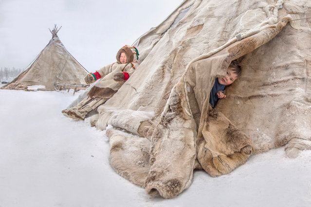 Kids are pictured in the Nenets, which consist of long sticks, and stitched reindeer skins stretched over it, pictured by Vladimir Alekseev in Russia, Yamal Peninsula. (Photo by Vladimir Alekseev/Travel Photographer of the Year)
