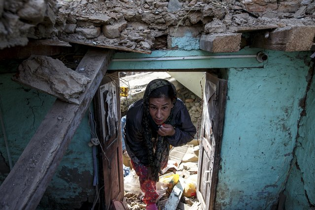 An earthquake survivor visits her collapsed house in Sankhu, on the outskirts of Kathmandu, Nepal, May 5, 2015. (Photo by Athit Perawongmetha/Reuters)