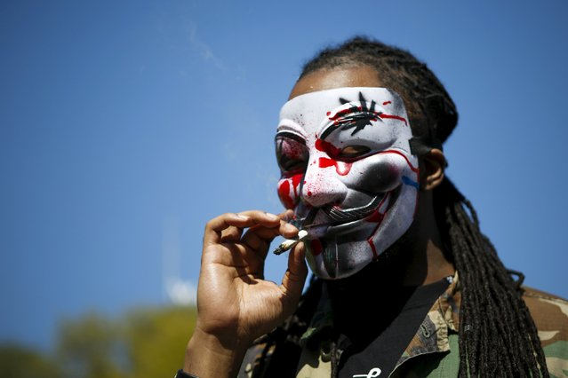 A man wearing a Guy Fawkes mask, smokes a joint while people take part in a rally calling for marijuana to be legalized, at Union Square in New York May 2, 2015. (Photo by Eduardo Munoz/Reuters)