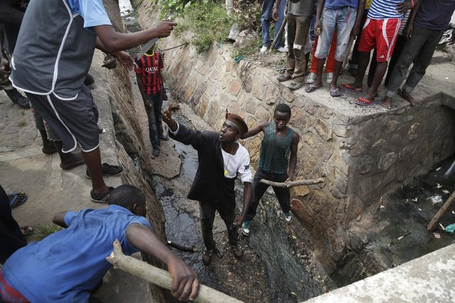 Demonstrators prepare to flush out Jean Claude Niyonzima a suspected member of the ruling party's Imbonerakure youth militia who escaped a lynching by escaping into a sewer in the Cibitoke district of Bujumbura, Burundi, Thursday May 7, 2015. (Photo by Jerome Delay/AP Photo)