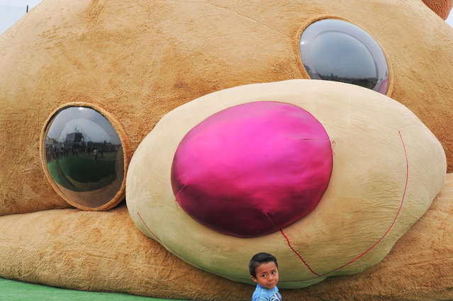 A little boy stands in front of a giant teddy bear measuring more than 20 meters long and 4 tons of weight, which entered the Guiness Book of World Records as the biggest of its kind on April 28, 2019 in Xonacatlan, Mexico state. (Photo by Mario Vazquez/AFP Photo)