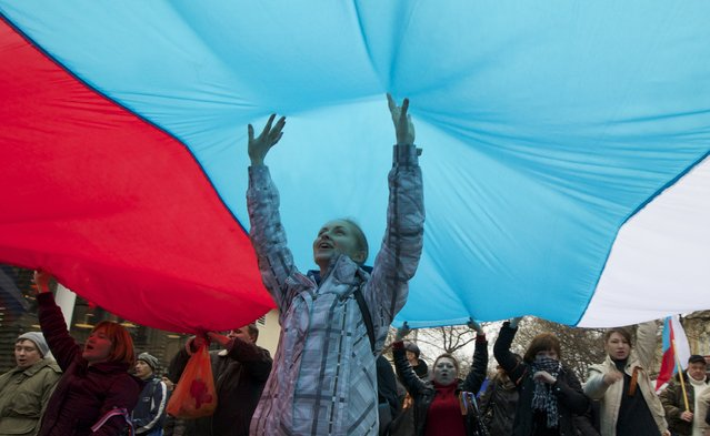 Local residents carry giant Russian flags and shout slogans rallying over the streets of Crimean capital Simferopol, Ukraine, on Saturday, March 1, 2014. (Photo by Ivan Sekretarev/AP Photo)