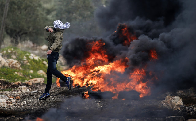 A Palestinian protester hurls stones at Israeli security forces, near a fire during clashes following a weekly demonstration against the expropriation of Palestinian land by Israel in the village of Kfar Qaddum, near Nablus, in the occupied West Bank on February 17, 2017. (Photo by Jaafar Ashtiyeh/AFP Photo)
