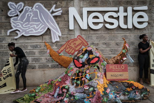 """Activisits of the environmental group Greenpeace Africa protest against Swiss food giant Nestle for their single-use plastic packages next to a """"plastic monster"""" object made with their plastic packaging, on April 16, 2019 bat the entrance of Nestle's factory in Nairobi, Kenya. According to Greenpeace Africa, last year, Nestle produced a 1.7 million tonnes of plastic packaging, nearly 300 garbage trucks worth a day.By their brand audits, Nestle was one of the top three plastic polluters in the world. (Photo by Yasuyoshi Chiba/AFP Photo)"""