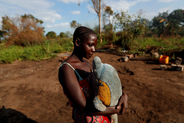 """Maria Jofresse, 25, holds a stuffed toy she received for her seventh birthday as she stands where her house stood, in the aftermath of Cyclone Idai, outside the village of Cheia, which means """"Flood"""" in Portuguese, near Beira, Mozambique April 2, 2019. Maria Jofresse lost her two children to the storm. In the midst of the floods, she dug their small graves but can't find them anymore. """"People suffered indeed but no one suffered as I did because I lost the most precious things I had – my kids"""", she said. (Photo by Zohra Bensemra/Reuters)"""