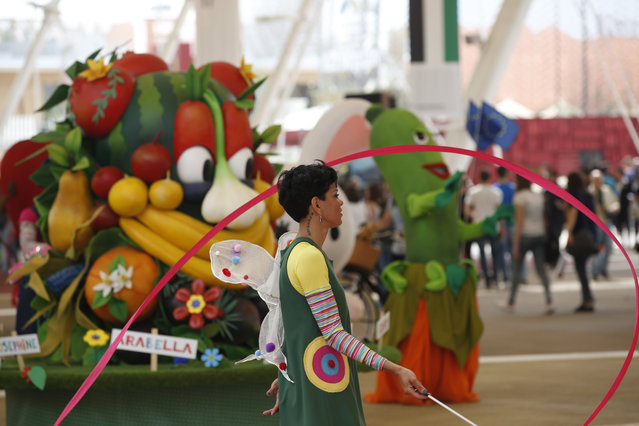 """Foody, background, left, the Expo mascot, is seen during the morning parade at the Expo 2015 in Rho, near Milan, Italy, Wednesday, May 13, 2015. The Expo 2015 world's fair opened Friday May 1 for a six-month run and its theme is """"Feeding the Planet, Energy for Life"""". (Photo by Luca Bruno/AP Photo)"""