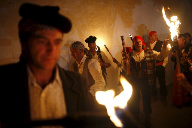 "People dressed as bandits hold torches as they participate in the third edition of ""Ronda Romantica"" (Romantic Ronda) in Ronda, southern Spain, May 16, 2015. (Photo by Jon Nazca/Reuters)"