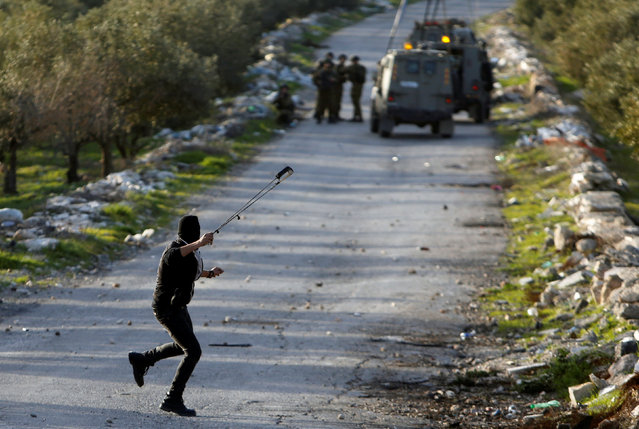 A Palestinian protester uses a sling to hurl stones towards Israeli troops during clashes in the West Bank village of Tuqu near Bethlehem February 26, 2017. (Photo by Mussa Qawasma/Reuters)