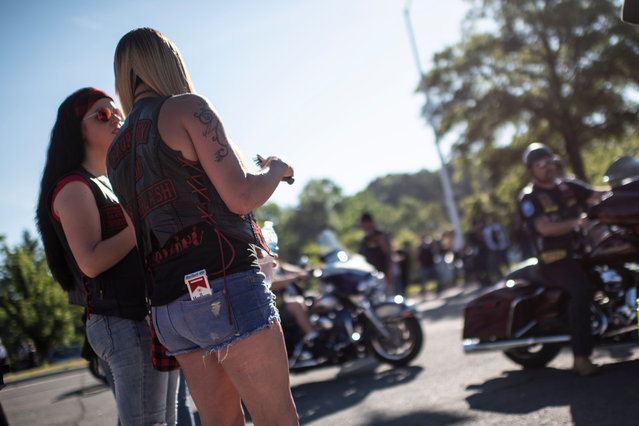 """Two biker ladies watch as hundreds of thousands of bikers gather on the Pentagon Parking before taking part in the """"Rolling thunder"""" parade, part of the Memorial weekend honouring war veterans in Arlington, near Washington, on May 26 2019. (Photo by Eric Baradat/AFP Photo)"""