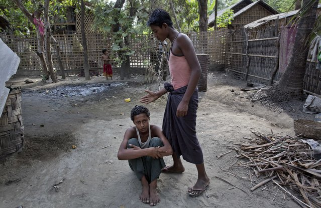 In this Monday, May 11, 2015, photo 16-year-old Sadik Hussein, left, and 17-year-old Noor Alam, roll-play as they retell how they were beaten at a human trafficking boat, hours after returning to their homes in Thetkabyin Village, north of Sittwe, western Rakhine state, Myanmar. (Photo by Gemunu Amarasinghe/AP Photo)