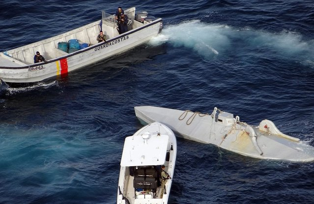 A handout photo released by Colombian Navy Force shows ships of Colombian Navy during the interception of a submersible (R) carrying six tons of cocaine on the sea border between Colombia and Ecuador, 13 April 2016. The operation was a joint operation with US Navy  through an agreement of interdiction among the countries. (Photo by EPA/Colombian Navy)