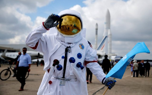 A man who works at Cobham Aerospace Communications company wears an astronaut suit at the 53rd International Paris Air Show at Le Bourget Airport near Paris, France on June 20, 2019. (Photo by Pascal Rossignol/Reuters)