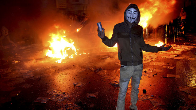 A masked protester poses with a tear gas canister in front of a burning vehicle during clashes between opponents of Egyptian President Mohammed Morsi and his Islamist supporters on December 21, 2012. (Photo by AP Photo)