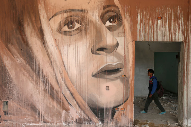 A schoolboy walks near a mural painted by Palestinian artist Ali Al-Jabali in the remains of a building destroyed in former Israeli air strikes, in Gaza City on April 25, 2019. (Photo by Ibraheem Abu Mustafa/Reuters)