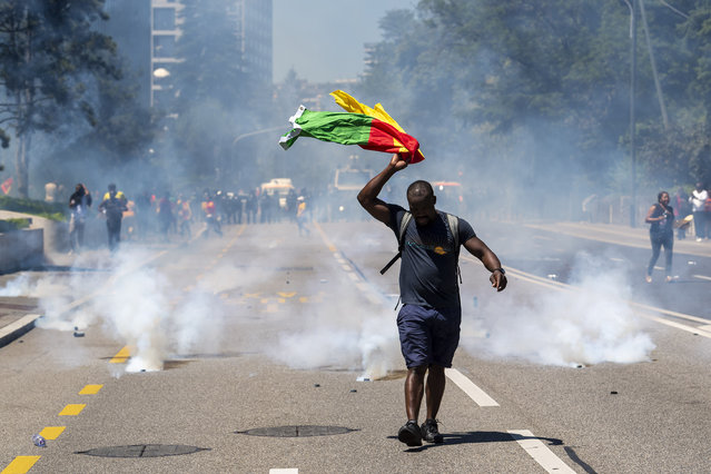 Police repel protesters with tear gas and water cannon, during Cameroonian nationals living in various European countries demonstrate against the presence of Cameroon President Paul Biya in Geneva, on the place des Nations in front of the European headquarters of the United Nations in Geneva, Switzerland, Saturday, June 29, 2019. (Photo by Martial Trezzini/Keystone via AP Photo)