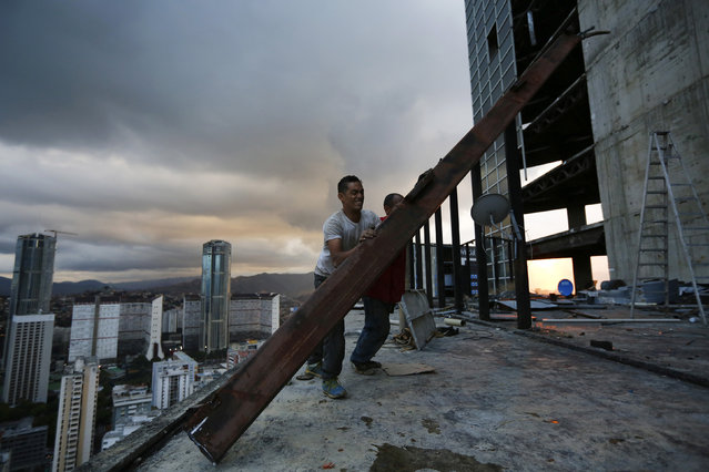 """Men salvage metal on the 30th floor of the """"Tower of David"""" skyscraper in Caracas February 3, 2014. (Photo by Jorge Silva/Reuters)"""