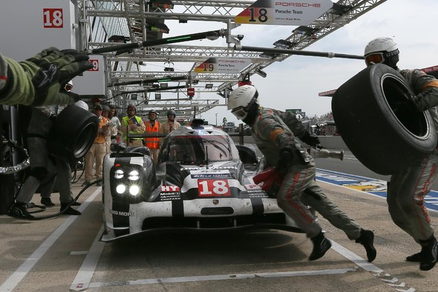 The Porsche 919 Hybrid No18 of the Porsche Team driven by Romain Dumas of France, Neel Jani of Switzerland and Marc Lieb of Germany make a stop in the stand during the 83rd 24-hour Le Mans endurance race, in Le Mans, western France, Saturday, June 13, 2015. (AP Photo/David Vincent)